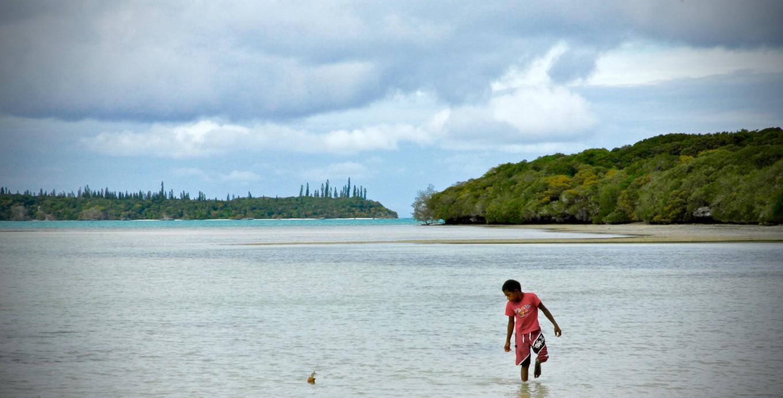Enfant jouant avec son bateau dans le lagon de l'île des pins, nouvelle-caledonie